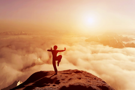 Foto de Asian man, fighter practices martial arts in high mountains above clouds at sunset. Kung fu and karate pose - Imagen libre de derechos