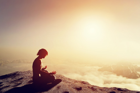 Photo pour Asian man meditates in yoga position in high mountains above clouds at sunset. Unique concept of meditation, spirituality, balance, harmony in life. - image libre de droit