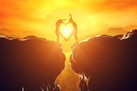 Foto de Happy couple making heart shape over precipice between two rocky mountains at sunset. Love unique concept. - Imagen libre de derechos