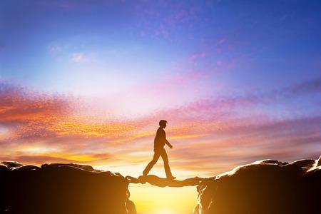 Photo pour Man walking over precipice between two mountains, another man serving as a bridge. Sunset, business conceptual - image libre de droit