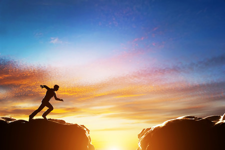 Photo pour Man running fast to jump over precipice between two mountains. Concepts of determination, business, challenge, success, risk etc. - image libre de droit