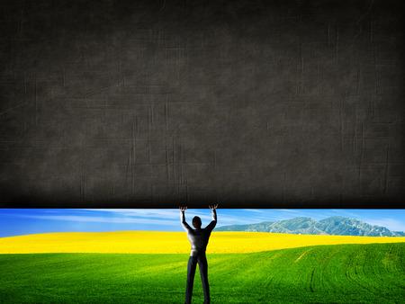 Foto de Man raising a concrete wall uncovering a new better world, green landscape. Concept. - Imagen libre de derechos