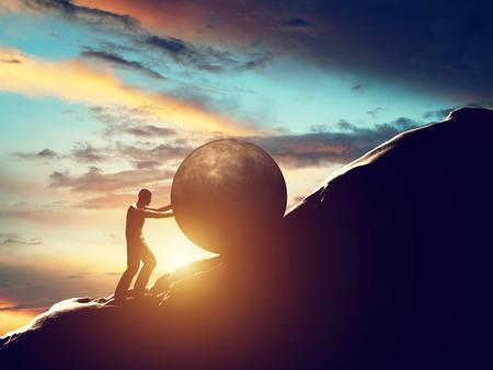Photo pour  Man rolling huge concrete ball up hill.  - image libre de droit