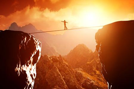 Foto de Man walking and balancing on rope over precipice in mountains at sunset - Imagen libre de derechos