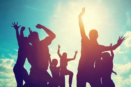 Foto de Happy friends, family jumping together in a circle having fun and expressing emotions of joy, freedom, success. Silhouettes on sunny sky - Imagen libre de derechos