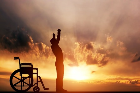 Foto de A disabled man standing up from wheelchair at sunset. Positive concept of cure, recovery, medical miracle, hope, insurance etc. - Imagen libre de derechos