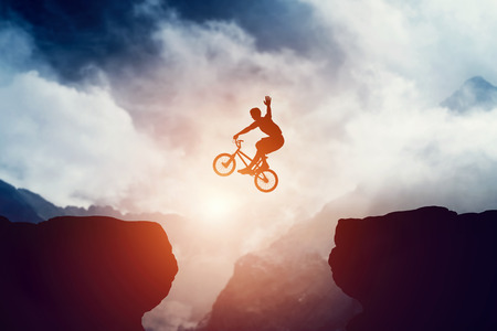 Foto per Man jumping on bmx bike over precipice in mountains at sunset. Raising hand showing hello gesture. Extreme sport, risk, cycling. - Immagine Royalty Free