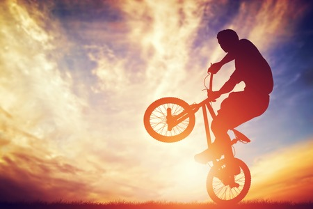 Foto de Man riding a bmx bike performing a trick against sunset sky. Extreme sport - Imagen libre de derechos