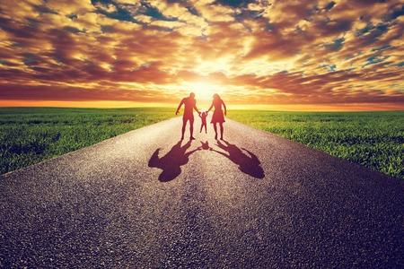 Foto de Family walk on long straight road, way towards sunset sun. Mother, father and child. Parenthood concepts - Imagen libre de derechos
