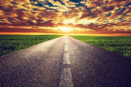 Foto de Long straight road, way towards sun. Sunset sky, travel, transport, destination concepts. - Imagen libre de derechos