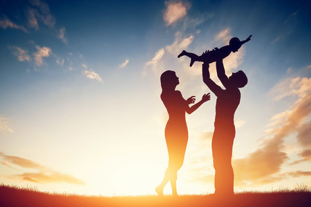 Foto de Happy family together, parents with their little child at sunset. Father raising baby up in the air. - Imagen libre de derechos