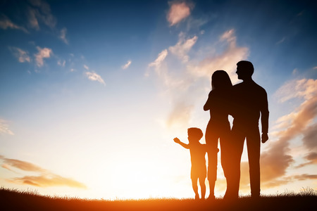 Photo for Happy family together, parents with their little child at sunset. Boy reaching the sun - Royalty Free Image