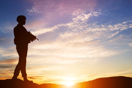 Foto de Armed soldier with rifle standing and looking on horizon. Silhouette at sunset. War, army, military, guard - Imagen libre de derechos