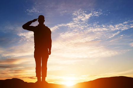 Foto de Soldier salute. Silhouette on sunset sky. War, army, military, guard concept. - Imagen libre de derechos