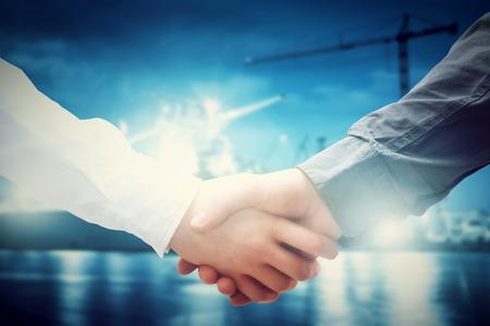 Photo pour Business handshake in shipyard, shipbuilding company. Industry, deal, contract. - image libre de droit