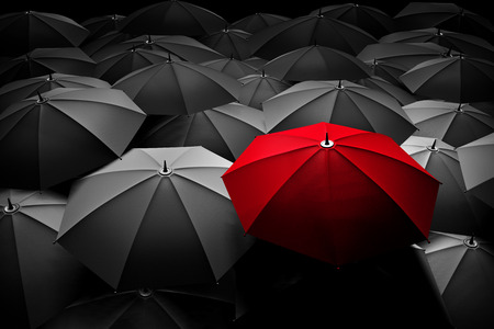 Photo pour Red umbrella stand out from the crowd of many black and white umbrellas - image libre de droit