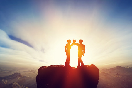 Photo for Two men, friends high five on top of the mountains. Agreement, positive energy, friendship concepts. Sunset sun light. - Royalty Free Image