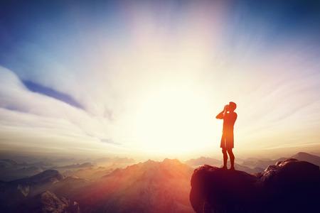 Foto de Man screaming on the top of the mounain at sunset. Concept of message, calling for help etc. - Imagen libre de derechos