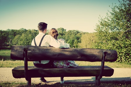 Photo for Young couple in love sitting together on a bench in summer park. Man wearing shirt with suspenders. Happy future, marriage concepts. Vintage - Royalty Free Image
