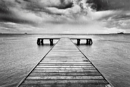 Photo for Old wooden jetty, pier on the sea. Raining from dramatic sky with dark, heavy clouds. Black and white - Royalty Free Image