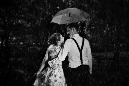 Foto de Young romantic couple in love flirting in rain, man holding umbrella. Dating, romance, black and white - Imagen libre de derechos