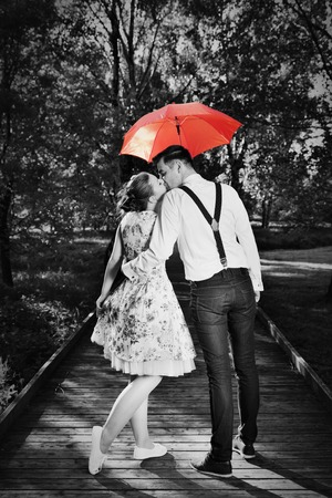 Photo for Young romantic couple in love flirting in rain, man holding red umbrella. Dating, romance, black and white - Royalty Free Image