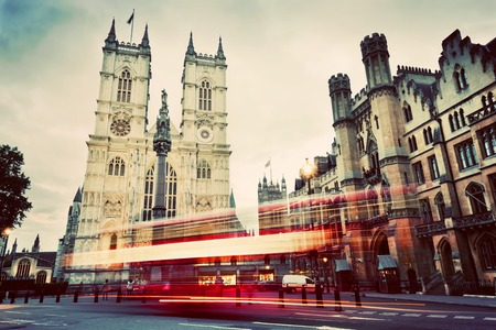 Photo pour Westminster Abbey church facade, red bus moving in London UK. Symbols of England, Great Britain. Vintage, retro style. - image libre de droit