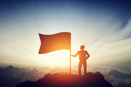 Foto de Proud man raising a flag on the peak of the mountain. Successful challenge concept, new achievement - Imagen libre de derechos