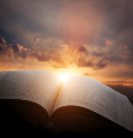 Foto de Open old book, light from the sunset sky, heaven. Fantasy, imagination, education, religion concept. - Imagen libre de derechos
