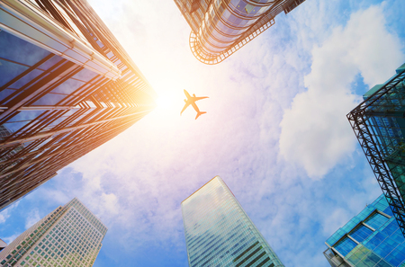 Foto für Airplane flying over modern business skyscrapers, high-rise buildings. Transport, transportation, travel. Sun light on blue sky. - Lizenzfreies Bild
