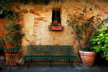 Foto de Retro bench outside old Italian house in a small town of Pienza, Italy. Plants decorations, vintage - Imagen libre de derechos