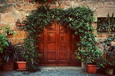 Photo pour Retro wooden door outside old Italian house in a small town of Pienza, Italy. Plants decorations, ivy, vintage - image libre de droit