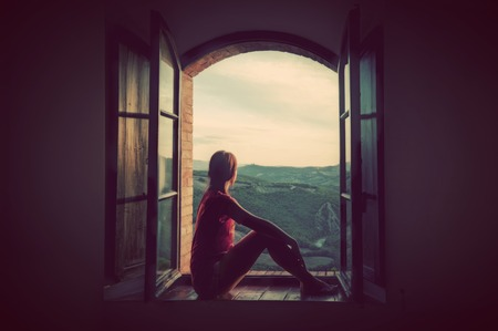 Foto de Young woman sitting in an open old window looking on the landscape of Tuscany, Italy. Conceptual romantic, dreaming, hope, travel. - Imagen libre de derechos