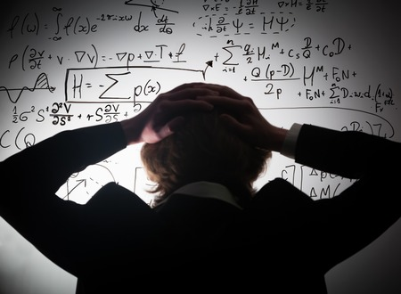 Foto de Student holding his head looking at complex math formulas on whiteboard. Mathematics and science exam concept, problem to solve. Real equations, symbols. - Imagen libre de derechos