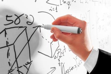Photo pour Man writing complex math formulas on whiteboard. Mathematics and science with economics concept. Real equations, symbols - image libre de droit