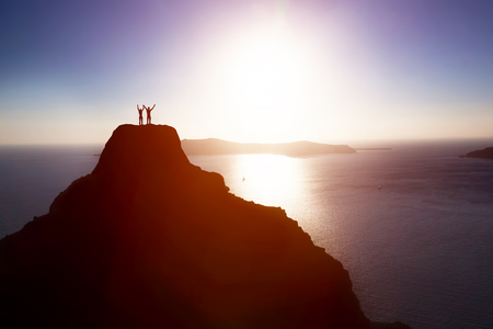 Photo pour Happy couple on the top of the mountain over ocean celebrating life, success. Concepts of winning together, achieving aim, positive energy. - image libre de droit