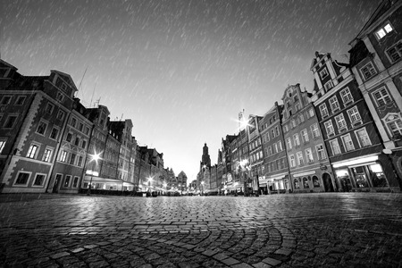 Foto de Cobblestone historic old town in rain. The market square at night. Wroclaw, Poland in black and white. Perfect empty space to put your object on the ground. - Imagen libre de derechos