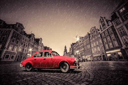 Photo for Retro red car on cobblestone historic old town in rain. The market square at night. Wroclaw, Poland. - Royalty Free Image