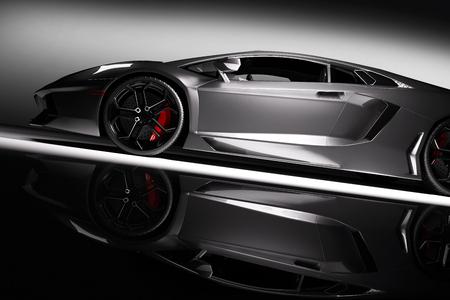 Foto de Grey fast sports car in spotlight, black background. Shiny, new, luxurious. 3D rendering - Imagen libre de derechos