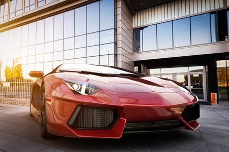 Photo pour Red fast sports car in modern urban setting. Generic, brandless design. 3D rendering - image libre de droit