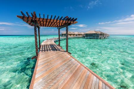 Foto de Wooden jetty towards water villas in Maldives. Resort on an island on Indian Ocean - Imagen libre de derechos