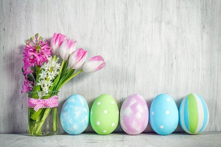 Photo pour Easter eggs and a spring bouquet of tulips on a wooden table. Springtime decoration. - image libre de droit