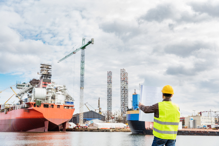 Foto de Shipbuilding engineer checking documents and plans of construction at the dockside in a port. Wearing safety helmet and yellow vest, holding folded papers. - Imagen libre de derechos