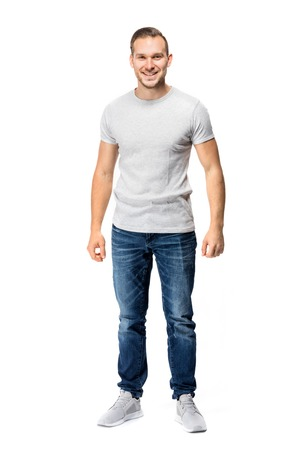 Photo for Handsome man in a white t-shirt, looking cheerful, smiling straight into the camera. Full body studio shot. - Royalty Free Image