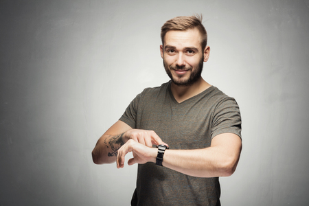 Photo for Handsome man pointing at a watch on the wrist. It's time concept - Royalty Free Image