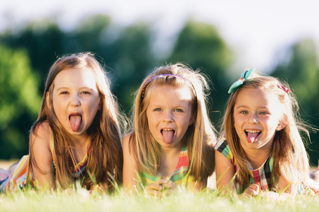 Photo pour Three little girls sticking their tongues out, laying on the grass in the park. Little rebels. Sisterhood. - image libre de droit