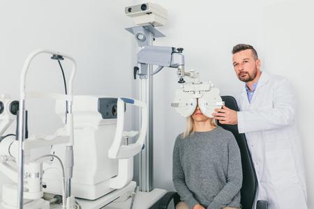 Foto de Eye doctor checking patient's eyes on a machine. Optometry, medical diagnosis. - Imagen libre de derechos