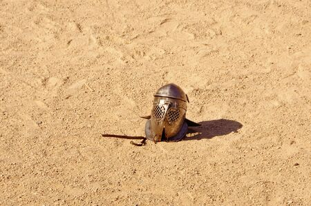 a helmet lying on the ground after a fight of gladiators