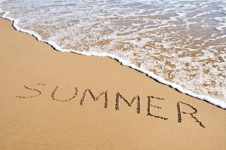 word summer written in the sand of a beach
