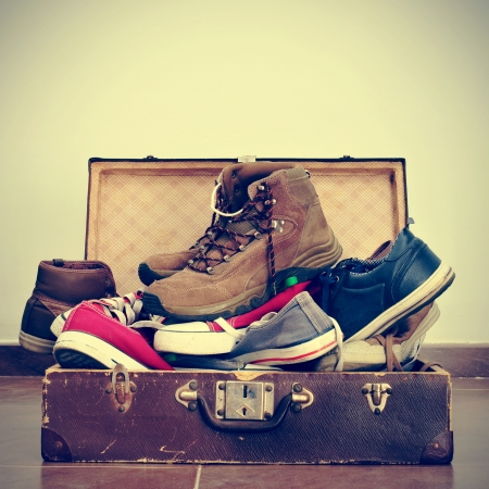 Photo pour a pile of shoes in an old brown suitcase with a retro effect - image libre de droit